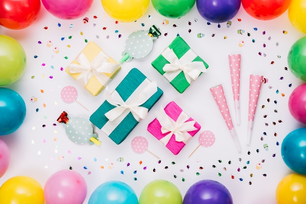 Caixas de presente coloridas; chifre de festa; adereço decorado com confetes e balões