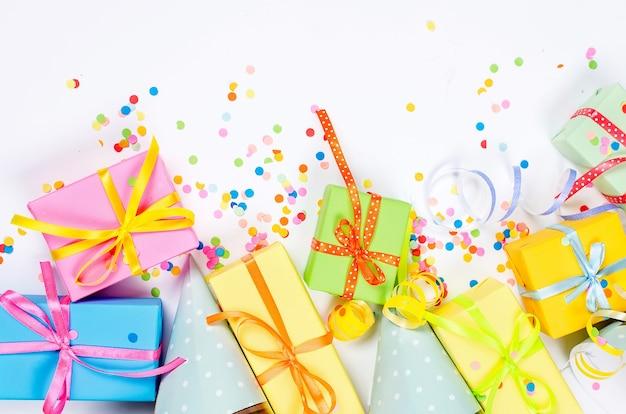 Caixas de presente coloridas, confete de papel e serpentina giratória de festa em um fundo branco