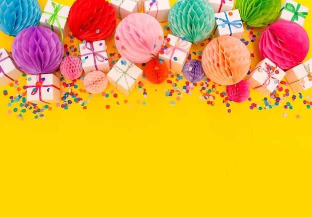 Caixas de presente coloridas e lanternas chinesas em uma vista superior de fundo amarelo.