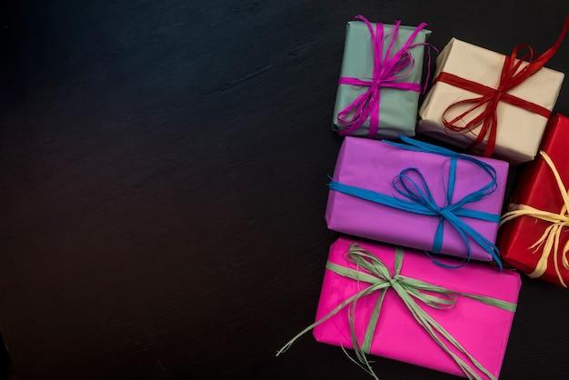 Caixas de presente coloridas em fundo escuro. comemoração de ano novo e natal