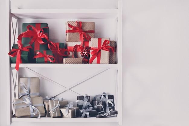 Caixas de presente coloridas embrulhadas em papel em prateleiras brancas no interior moderno.