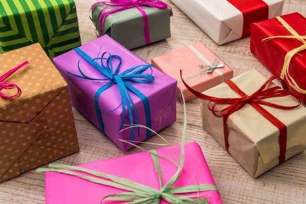Caixas de presente coloridas na vista superior da mesa de madeira. presentes, ano novo e festa de natal