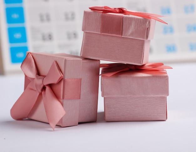Caixas de presente com calendário de mesa em fundo branco. compras de fim de ano, sexta-feira negra, conceito de oferta especial mensal
