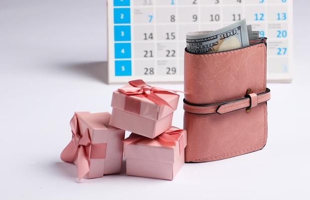 Caixas de presente com carteira, calendário de mesa em fundo branco. compras de fim de ano, sexta-feira negra, conceito de oferta especial mensal