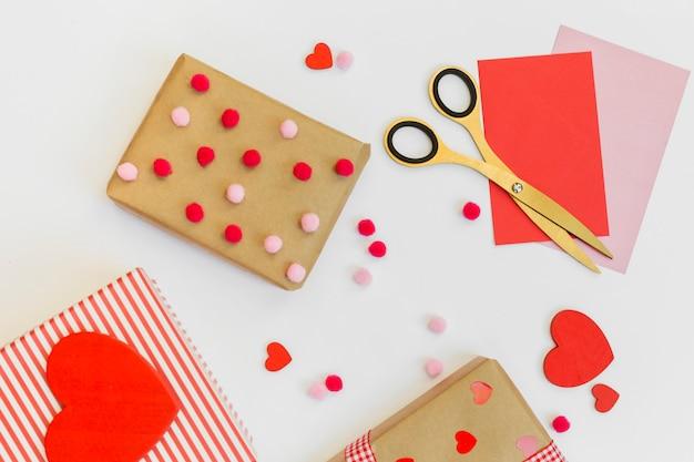 Caixas de presente com corações vermelhos e envelopes na mesa
