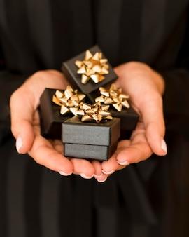 Caixas de presente com fita dourada para vista frontal preta na sexta-feira