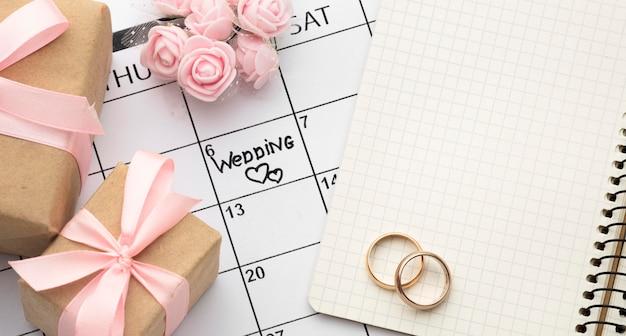 Caixas de presente com fita rosa e anéis de casamento
