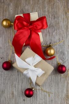 Caixas de presente com fitas de cetim vermelhas e brancas na mesa de madeira