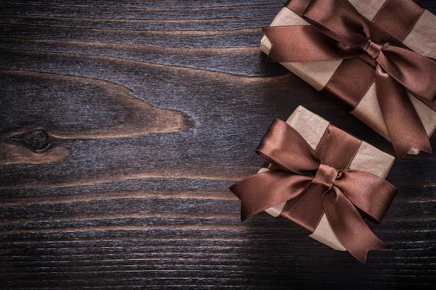 Caixas de presente com fitas marrons na placa de madeira vintage