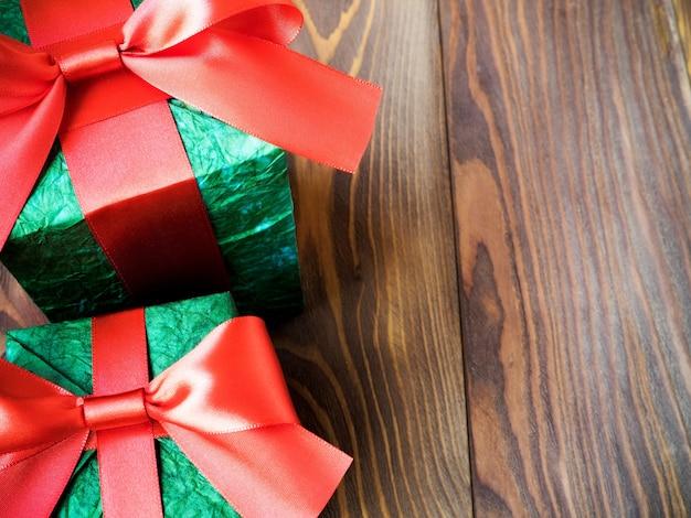 Caixas de presente com fitas vermelhas na placa de madeira. conceito de férias