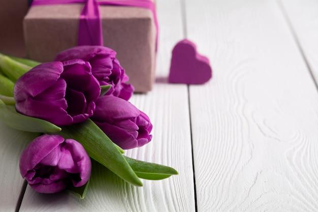 Caixas de presente com flores na parede de madeira branca
