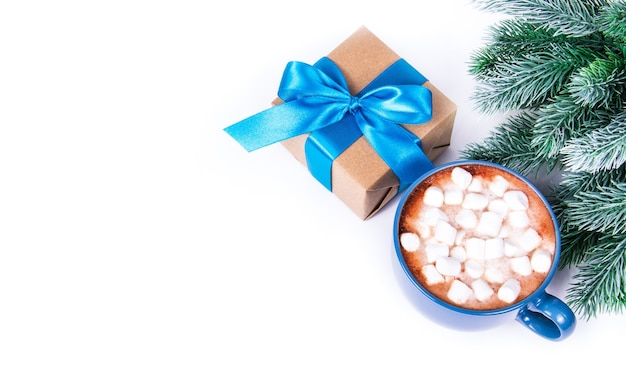 Caixas de presente com galhos de pinheiro ao lado e xícara de chocolate com marshmallow