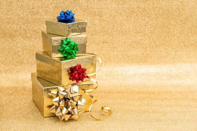 Caixas de presente com laço de fita em fundo dourado. decoração de festas Foto Premium