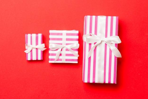 Caixas de presente com laços brancos sobre fundo vermelho.