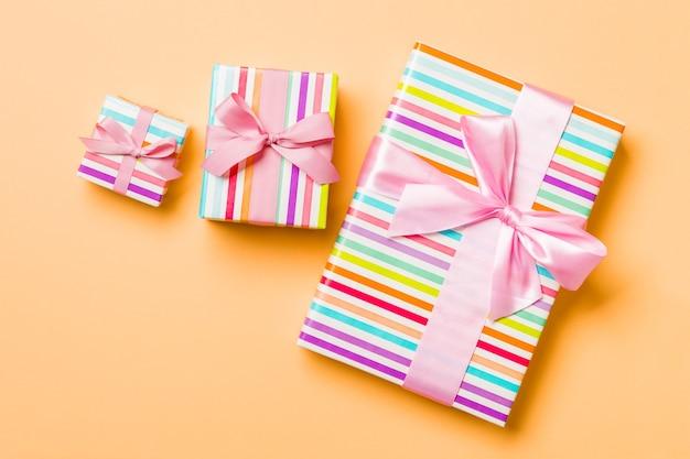 Caixas de presente com laços cor de rosa em fundo laranja.