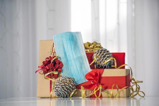 Caixas de presente com laços e fitas, cones de abeto e máscara protetora. férias de inverno seguras