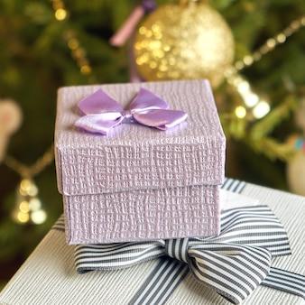Caixas de presente com laços nas tampas sob uma árvore de natal na véspera de ano novo