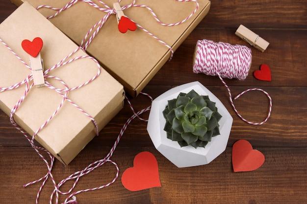 Caixas de presente com pinos de pano com corações vermelhos e suculentas em pote de concreto em um fundo de madeira