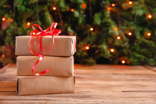 Caixas de presente com um grande laço vermelho contra um bokeh de fundo de luzes cintilantes de festa. presente de natal.