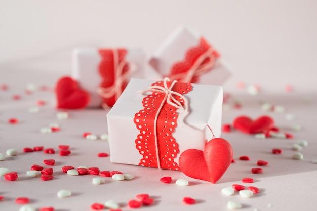 Caixas de presente de dia dos namorados com presentes e decorações. em fundo rosa com granulado.