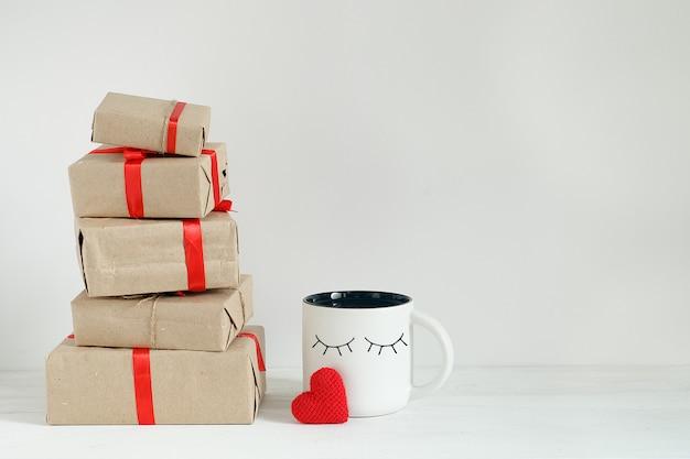 Caixas de presente de dia dos namorados, coração de brinquedo e xícara de café com mais bonitos olhos engraçados