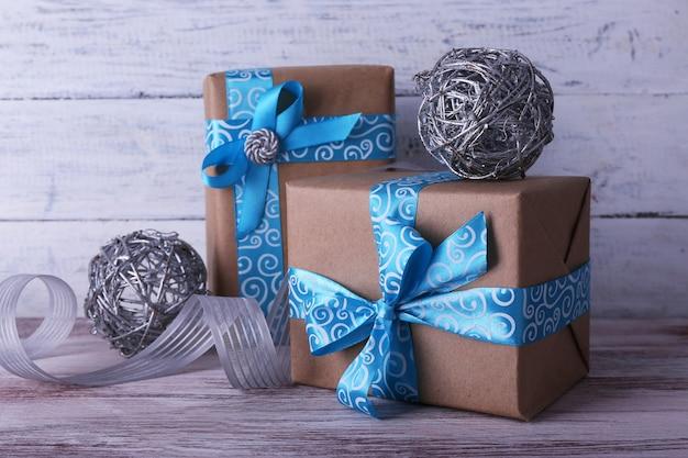 Caixas de presente de feriado decoradas com fita azul na mesa na parede de madeira