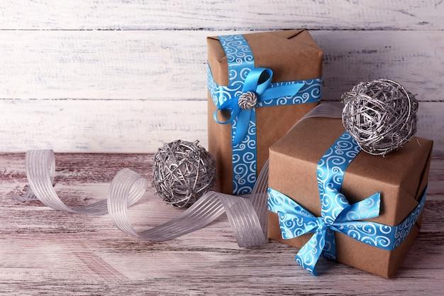Caixas de presente de feriado decoradas com fita azul na mesa no fundo da parede de madeira