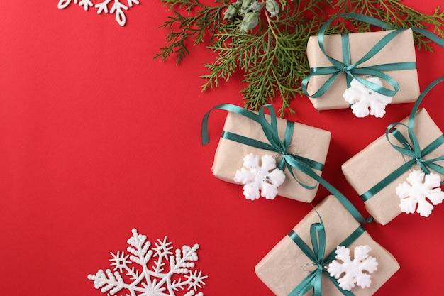 Caixas de presente de natal com fita verde na superfície vermelha.