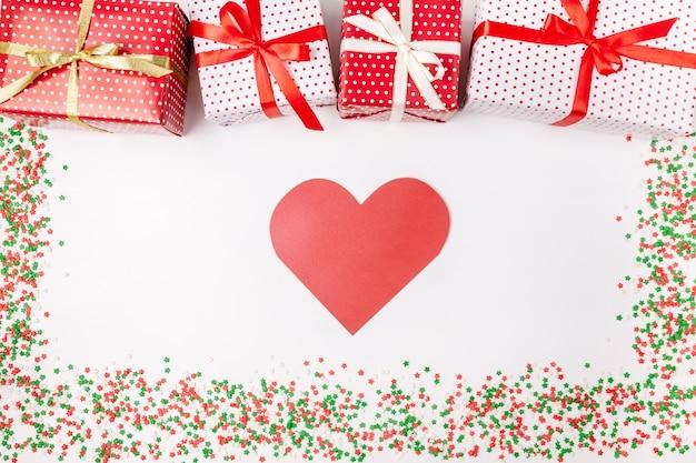 Caixas de presente de natal com fitas, cartão em forma de coração e brilhos em branco