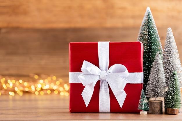 Caixas de presente de natal com fitas e árvore em bokeh de fundo.