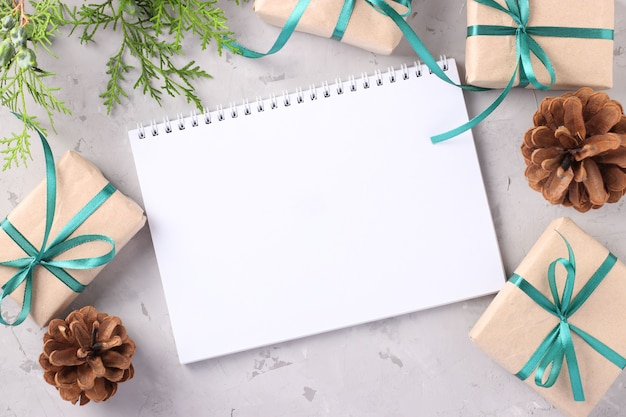 Caixas de presente de natal com fitas verdes na superfície cinza. espaço para desejos.