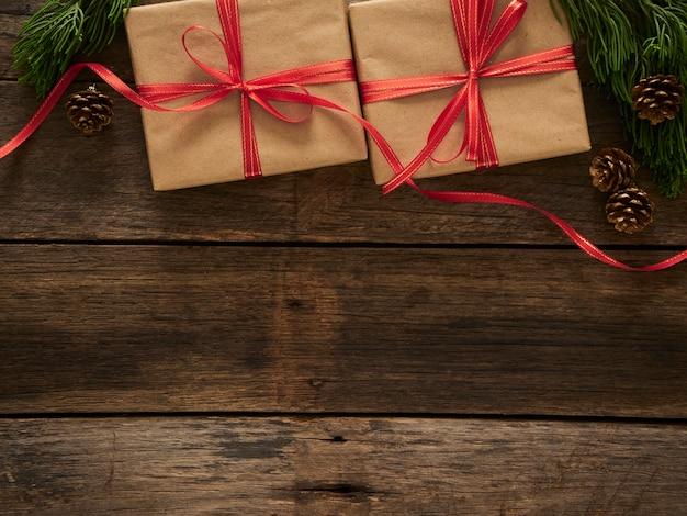 Caixas de presente de natal com galhos de pinheiros e enfeites em fundo rústico de madeira escura