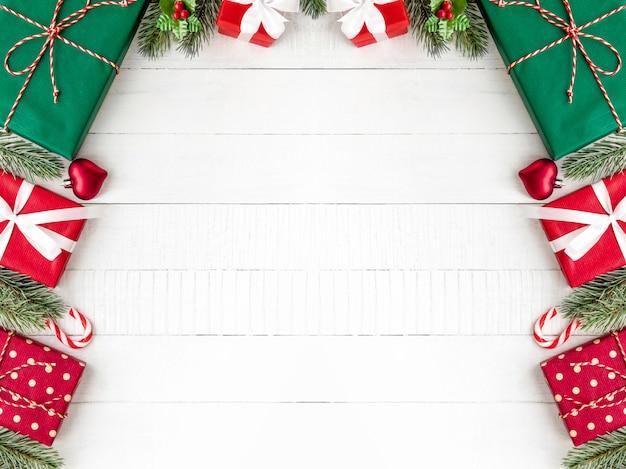Caixas de presente de natal com pinheiros e enfeites de decoração em fundo branco de madeira