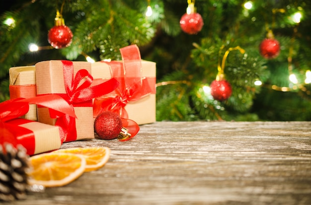 Caixas de presente de natal contra o da árvore de natal e bokeh de luzes cintilantes do partido.