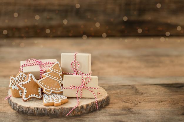 Caixas de presente de natal e biscoitos de gengibre em uma superfície de madeira