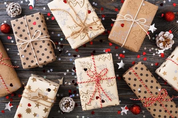 Caixas de presente de natal e decorações de brilho na mesa festiva.