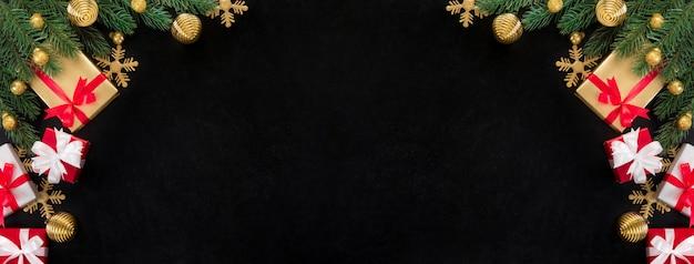 Caixas de presente de natal e enfeites de decoração dourados brilhantes sobre fundo de quadro-negro