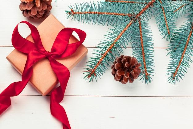 Caixas de presente de natal e galho de árvore do abeto na mesa de madeira.