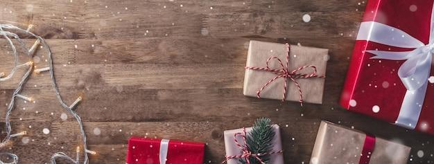 Caixas de presente de natal e luz da corda no fundo da bandeira de madeira