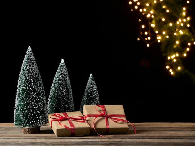 Caixas de presente de natal e pinheiro na mesa de madeira contra luzes festivas borradas, espaço para texto