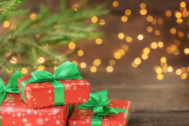 Caixas de presente de natal em fundo de madeira com luzes desfocadas