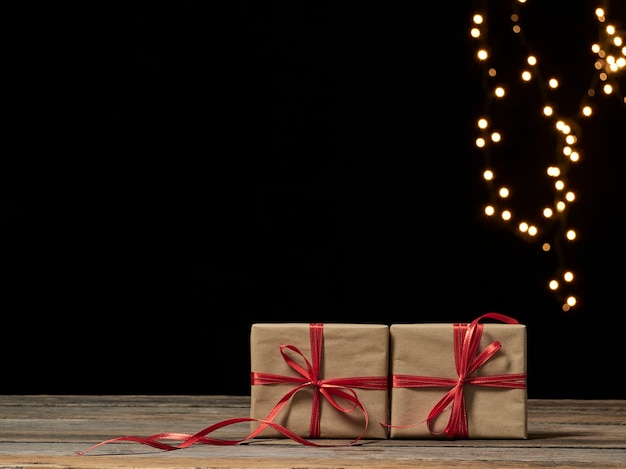 Caixas de presente de natal na mesa de madeira contra luzes festivas borradas, espaço para texto