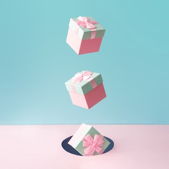 Caixas de presente de natal rosa pastel em pano de fundo azul e rosa.