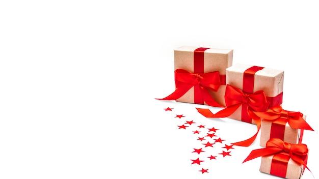 Caixas de presente de papel ofício com laço de fita vermelha, confete estrela isolado