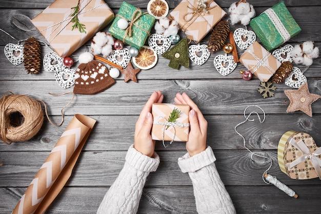 Caixas de presente, decorações de natal e pinhas na mesa de madeira cinza
