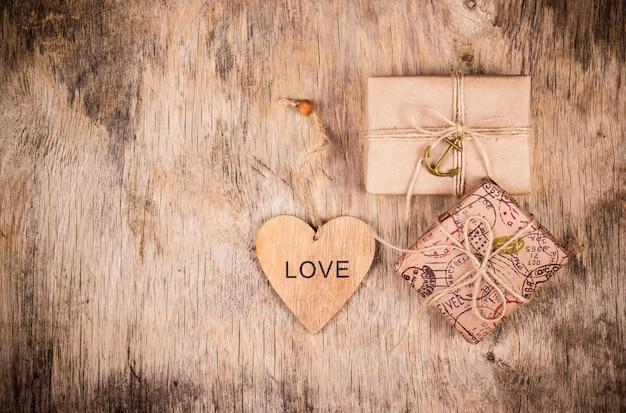 Caixas de presente e coração na placa de madeira
