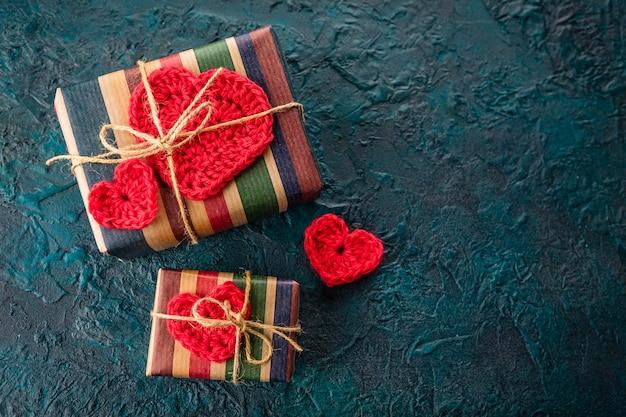 Caixas de presente e corações dos namorados de crochê no bacground branco.