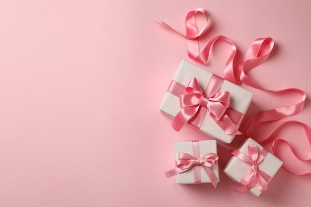 Caixas de presente e fita em fundo rosa