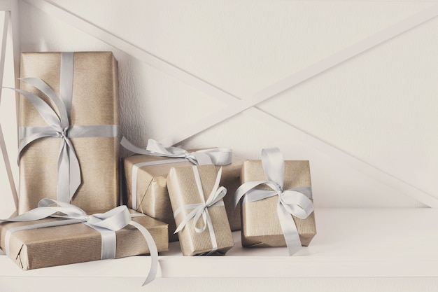 Caixas de presente elegantes com fita de cetim embrulhada em papel.
