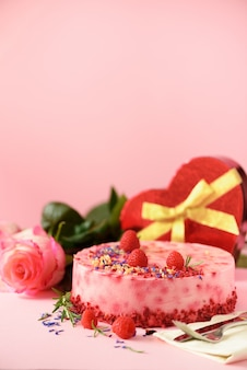 Caixas de presente em forma de coração, rosas, bolo de framboesa com frutas frescas, alecrim e flores secas. conceito de dia dos namorados. presente com amor